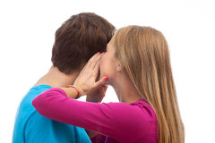 Whispering in the ear. Girl whispering in the ear to her boyfriend Stock Photo
