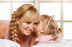 Whispering little girl and mother Royalty Free Stock Photos