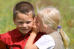 Whispering and smiling. Girl whispering secret to a smiling boy Stock Images