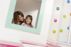Whispering and storytelling. Mother and daughter playing in a playroom, hiding in a small wooden house, whispering and storytelling. Focus on the daughter royalty free stock images