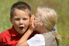 Whispering and stunned. Girl whispering secret to a stunned boy Royalty Free Stock Image