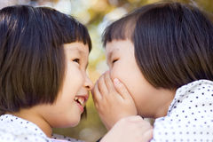 Whispering twin girls Royalty Free Stock Photos