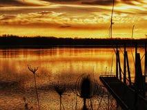 Whisps d'or des nuages au-dessus de la rivière rougeâtre profonde d'or image libre de droits
