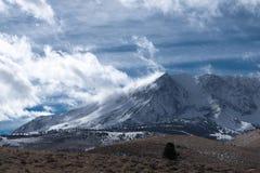 Whispy białe chmury tworzą z śnieżnego szczytu Obraz Royalty Free