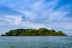 No man is an island like this island in Parque Vargas, Limon, Co. Whispy clouds float above a lush green rain forest island in Parque Vargas, Limon, Costa Rica stock images