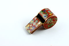 Decorative tin whistle. With colorful Asian pattern, white background stock image