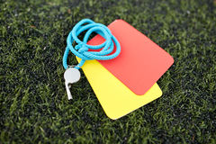 Whistle and caution cards on football field Stock Photos