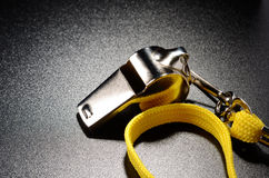 Whistle. Metal whistle on a black grained surface Royalty Free Stock Photography