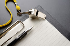 Whistle. Metal sport whistle with pen and paper sheet Royalty Free Stock Photography