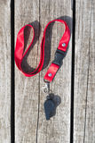 Whistle on a red ribbon lying on wooden boards royalty free stock photo