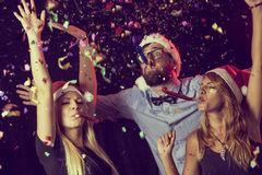 Whistle. Three young people blowing party whistles at a New Year's Eve party Royalty Free Stock Images