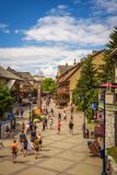 Street view with many tourists  in Whistler Village. WHISTLER, BRITISH COLUMBIA, CANADA - JULY 2, 2017 : Scenic street view with many tourists  in Whistler Royalty Free Stock Image