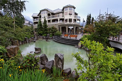 Whistler Building and Lake. A charming green lake with yellow flowers and a wood building in Whistler village, British Columbia, Canada Royalty Free Stock Photo