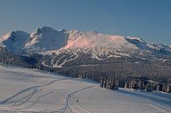 Whistler Mountain site of 2010 Winter Olympics. Early light on ski run and Coast Range mountains Royalty Free Stock Photos