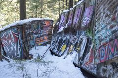 Whistler Train wreck site with grafitti painted rail cars. 60 year old wrecked graffiti covered rail cars are nestled among forest trees at the Whistler train stock photography