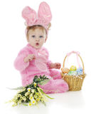 Whistling Easter Bunny. An adorable baby girl attempting to whistle in her fluffy pink Easter bunny outfit.  She sits beside a basket of colored eggs and a small Stock Photo