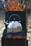 The whistling kettle begins to boil on a brazier Royalty Free Stock Image