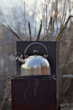 The whistling kettle begins to boil on a brazier. Stock Photo