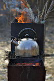 The whistling kettle begins to boil on a brazier. Royalty Free Stock Photos