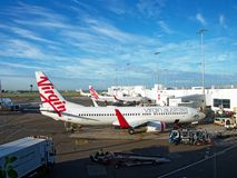 Jet Aircraft at Sydney airport,  Australia. Whit painted Virgin Australia jet aircraft parked at air bridges at Sydney  domestic  airport with maintenance royalty free stock images