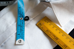 Whit shirt with measuring tape, wooden scale and buttons. White shirt on a black fabric, buttons, wooden scale and blue measuring tape. Basics for well fitting Stock Images