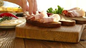 Whit van Sandwick de kaas van het baconeind Zwart brood met bacon en kruiden Kaas met gaten op de plaat Dun gesneden varkensvlees stock video