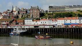 Whitby - North Yorkshire - England. Pleasure boat in the port of Whitby on the North Yorkshire coast in northeast England. Harbor at low tide stock footage