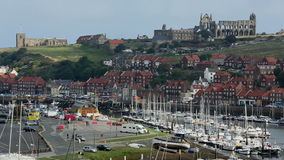 Whitby - North Yorkshire - England. The port of Whitby on the North Yorkshire coast in northeast England, with the ruins of Whitby Abbey on the hillside above stock video