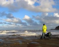 Whitby seascape. Angler watches waves in Whitby. North Yorkshire, UK stock photo