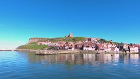 The Whitby Waterfront in Northern England. The view across the Whitby waterfront, a North Yorkshire seaside town in northern England.  The church of St Mary can stock footage