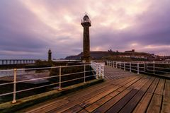 Whitby West Pier Light in Yorkshire. The Historic Whitby West Pier Light looking towards Whitby Abbey and St Hilda`s Church in Yorkshire stock photo