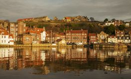 Whitby, Yorkshire, England - the orange houses. This image shows some houses in Whitby, Yorkshire. It was taken at sunset, we can see the reflection of the Royalty Free Stock Image
