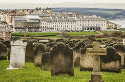 Whitby, Yorkshire, England - the wiev from a cemetery. The image shows a view of Whitby, a small town in Yorkshire, England - it focuses on some stone graves in Royalty Free Stock Images