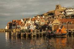 Whitby, Yorkshire, Inglaterra - as casas iluminaram-se pela luz do sol foto de stock