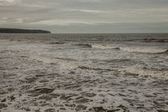 Whitby, Yorkshire - veranderlijke wateren van het overzees en de donkere hemel Stock Afbeelding