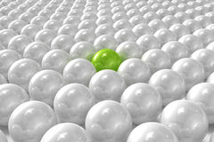 White 3D balls with green one standing out. High quality 3D render of white 3D balls with green one standing out Stock Photography