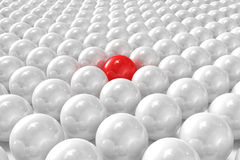 White 3D balls with red one standing out. High quality 3D render of white 3D balls with red one standing out royalty free illustration