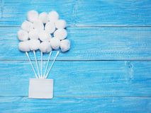 White absorbent cotton balls and cotton buds on wooden blue background royalty free stock photography
