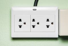 White AC Electric Outlet with Indicator Lamp on Green Wall Royalty Free Stock Photos