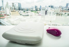 White access point with purple mouse on office desk Stock Image