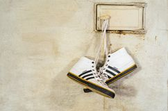 White Adidas Sneakers Hang on Laces. Minsk, Belarus - September 29, 2017: White Adidas Sneakers Hang on Laces and Dry on a Russian Stove, Close-up Royalty Free Stock Photo