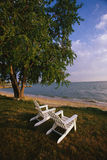White adirondack chairs facing ocean. This is the Eastern Shore of Maryland. These are white wooden deck chairs sitting on the lawn. They are looking out over Royalty Free Stock Photo