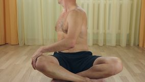 White adult caucasian man do exercise indoors at living room. Turn body back stretching vertebra. stock video footage
