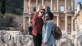 White and African couple taking a selfie in front of the Celcus library. White and African couple taking a selfie in front of the Celcus library at Ephesus stock footage