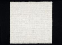 White Aida cloth canvas. A white, square and plain, unused piece of Aida cloth, the kind of canvas used for cross-stich works, on black background Royalty Free Stock Photos