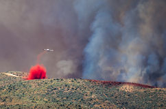 White Aircraft Dropping Fire Retardant as it Battles the Raging Wildfire Royalty Free Stock Photo