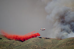 White Aircraft Dropping Fire Retardant as it Battles the Raging Wildfire Stock Images