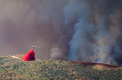 White Aircraft Dropping Fire Retardant as it Battles the Raging Wildfire Stock Photography