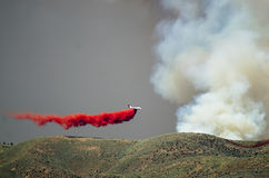 White Aircraft Dropping Fire Retardant as it Battles the Raging Wildfire Royalty Free Stock Photography