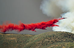 White Aircraft Dropping Fire Retardant as it Battles the Raging Wildfire Royalty Free Stock Image